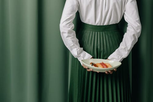 Person in White Long Sleeve Shirt and Green Skirt Holding Orange Fruit