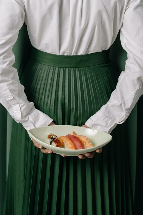 Person in Green and White Stripe Dress Holding a Plate With Sliced of Bread