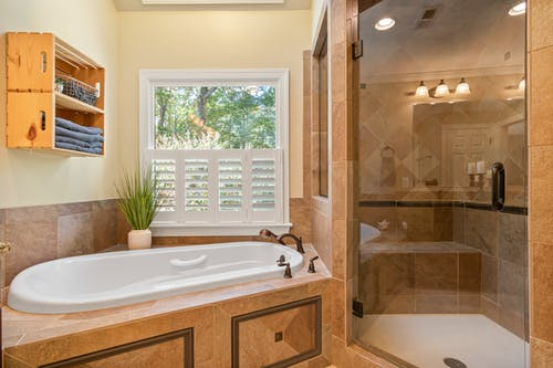 White Ceramic Bathtub Near Brown Wooden Framed Glass Door