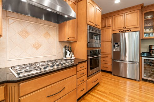 Silver French Door Refrigerator Beside Brown Wooden Kitchen Cabinet