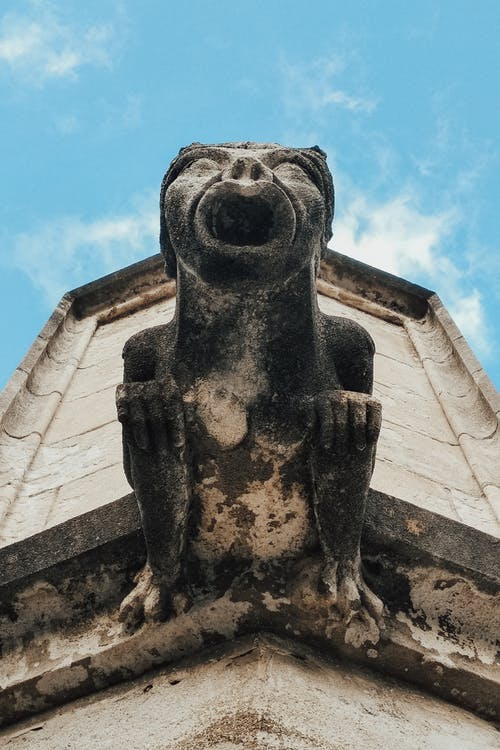 From below of shabby stone statue of gargoyle on wall of aged construction under blue sky