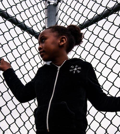 Girl in Black Jacket Standing Beside Gray Metal Fence