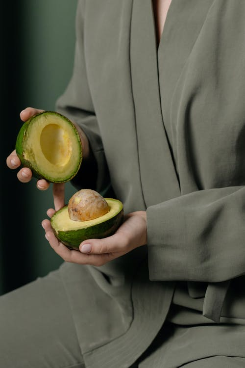 Person Holding A Sliced Green Avocado