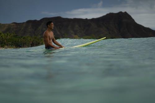Surfer resting on surfboard in sea