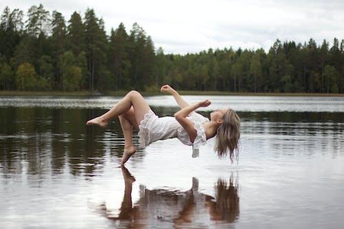 Foto d'estoc gratuïta de aigua, calma, dona, flotant