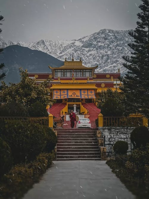 Brown and White Temple Near Green Trees and Mountain