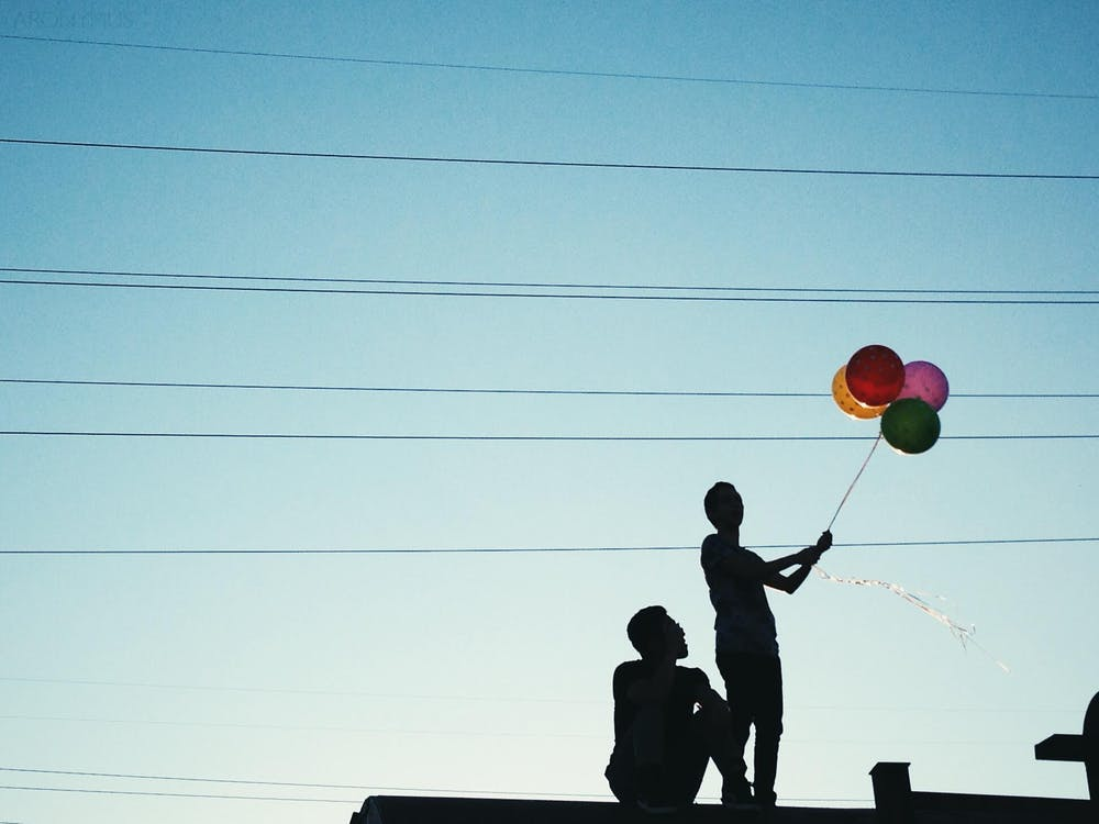 Men Holding Red Pink and Yellow Balloon Under Blue Sky during Daytime