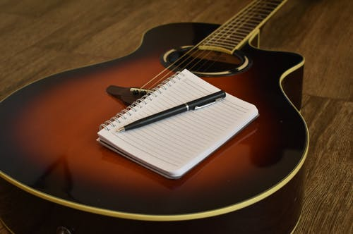 Free stock photo of guitar, notebook, notebook and guitar, songwriter