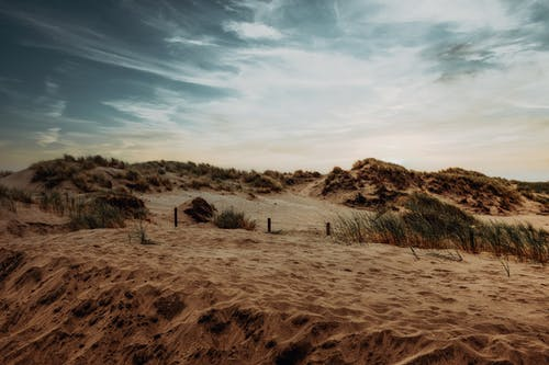 Brown Sand Under White Clouds and Blue Sky