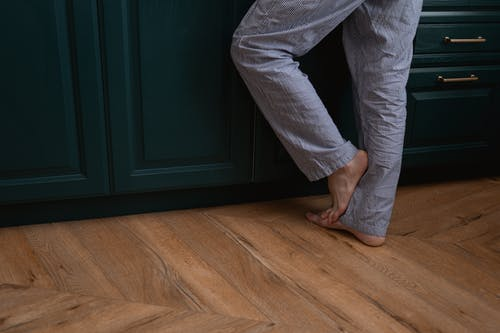 Person Standing on the Wooden Floor with Barefoot