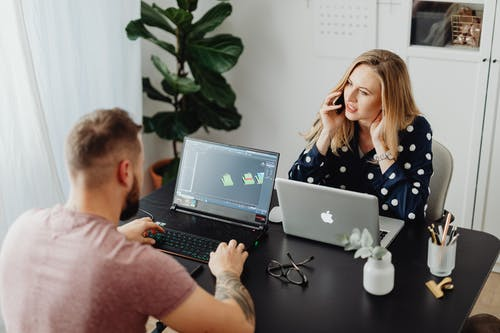 Man and Woman Using Laptop on the Table