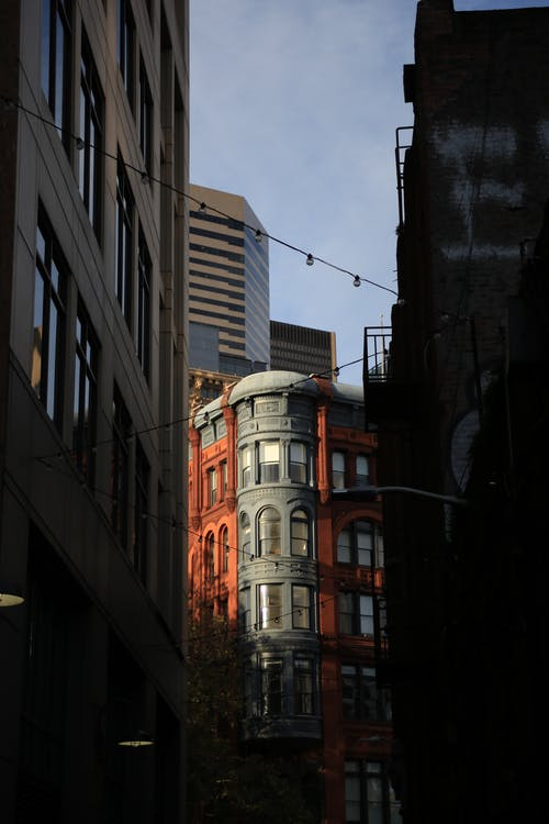 Modern and aged multistory building exteriors on dark street under sky with clouds in city