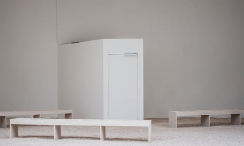 White building walls and door near benches on floor in light empty place