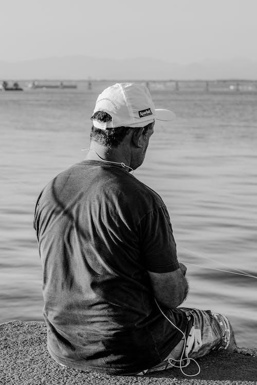 Man sitting on border of shore near river