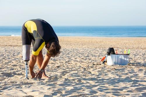 Erwachsener Mann Mit Prothetischem Bein, Das Am Strand Aufwärmt