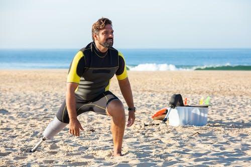 Man with leg prosthesis training on sandy beach