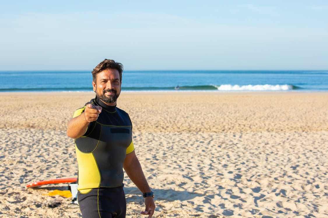 Happy male in diving suit looking and pointing at camera while standing on beach in bright sunny day