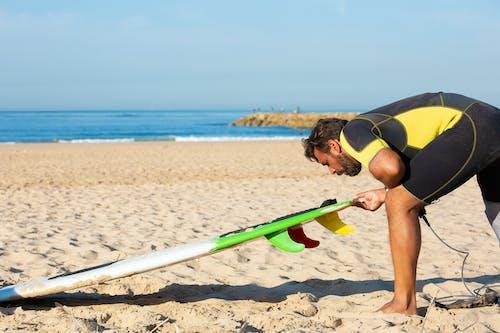 Man in wetsuit preparing surfboard for ride on beach
