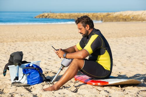 Man with prosthesis using smartphone on beach