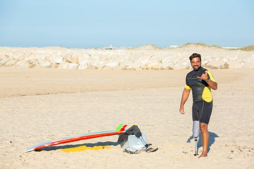 Full body content ethnic amputee male surfer wearing wetsuit standing on sandy beach and showing shaka sign while looking at camera with smile
