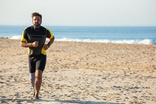 Full body energetic ethnic male with leg prosthesis in activewear jogging on sunny sandy seashore against calm sea and looking at camera