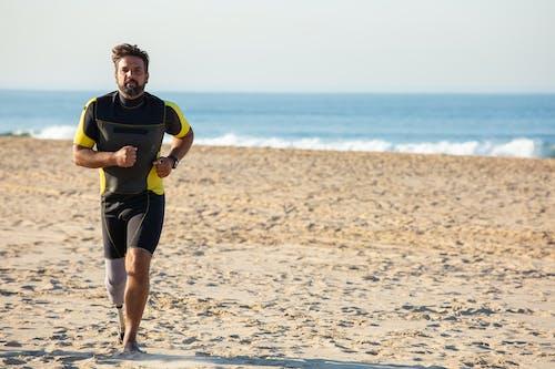 Dedicated ethnic sportsman amputee jogging on sandy coastline