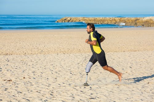 Determined sportsman with leg prosthesis running on sandy coastline