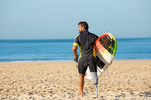 Back view full body muscular male surfer with leg prosthesis standing with surfboard on sandy sunny seashore and looking away