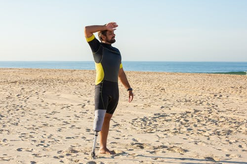 Sportsman amputee wiping sweat while standing on sandy coast