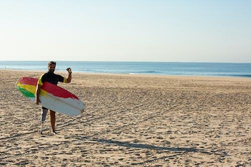 Surfer Homme Fort Amputé Montrant Le Geste De Poing Levé Sur La Plage