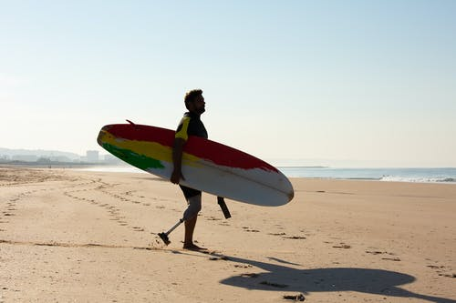Side view full body silhouette of male surfer with amputated leg carrying surfboard and walking along sandy seashore near waving sea on sunny weather
