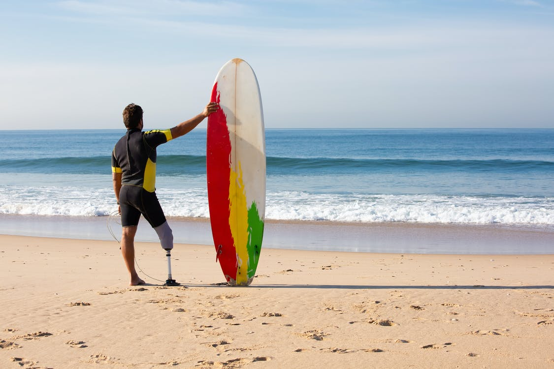 Unrecognizable amputee man surfer with surfboard standing on seashore