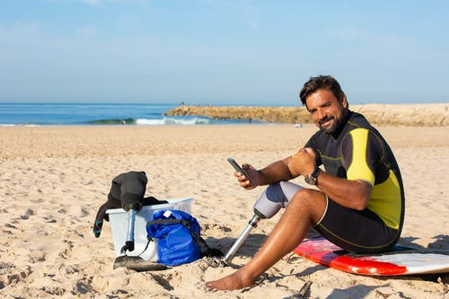 Contenido Surfista Masculino Amputado étnico Con Smartphone En La Playa