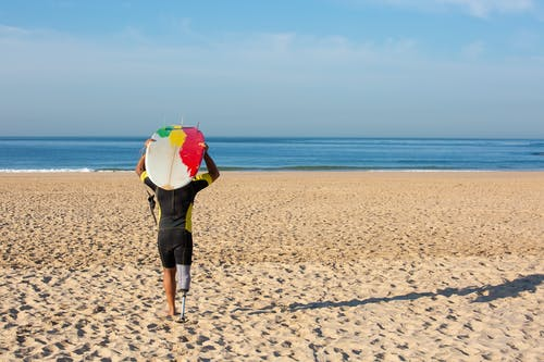 Unrecognizable amputee male surfer carrying surfboard on head towards sea