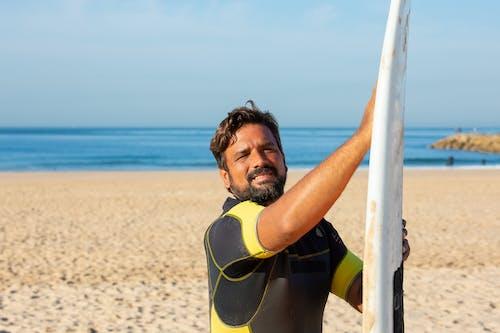 Surfeur Masculin Positif Debout Avec Planche De Surf Sur La Plage De Sable