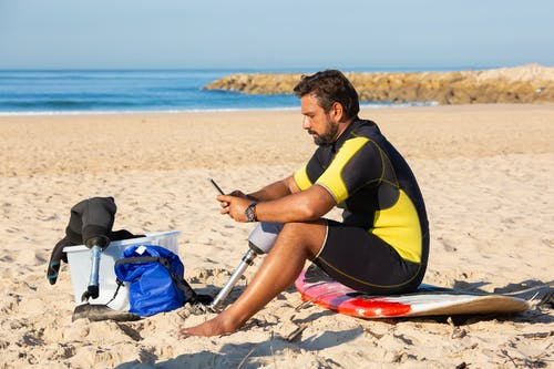Focused ethnic sportsman with leg prosthesis using smartphone on beach