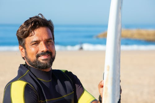 有站立在晴朗的海岸線的衝浪板的愉快的種族男性衝浪者