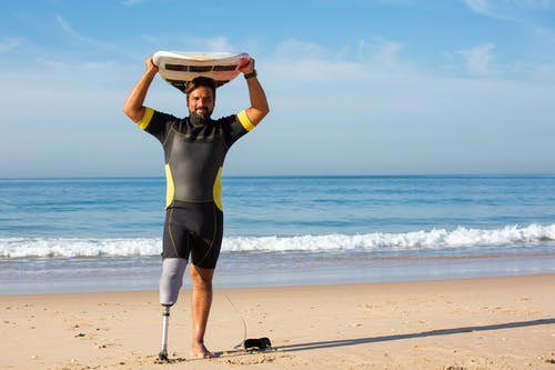 Full body glad ethnic male surfer with leg prosthesis standing on sandy beach against azure sea and holding surfboard above head while looking at camera