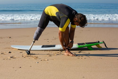 Full length sporty tanned male surfer with leg prosthesis tying surfboard leash around ankle while standing on sandy seashore before surfing