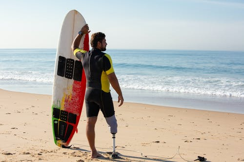 Male amputee surfer standing with surfboard on beach