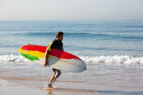 Dedicated amputee male surfer with surfboard walking towards waving sea