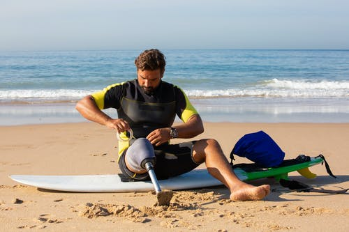 Full body focused amputee male surfer sitting on surfboard on sandy beach and wrapping prosthesis socket with tape before surfing