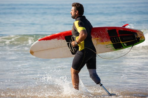 Sporty male surfer amputee with surfboard running in shallow seawater