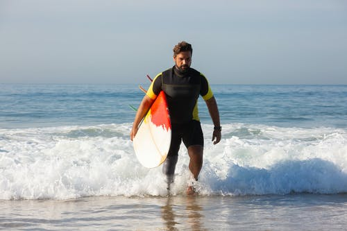Full body sporty ethnic male surfer with leg prosthesis carrying surfboard and walking in foamy seawater towards sandy shore on sunny day