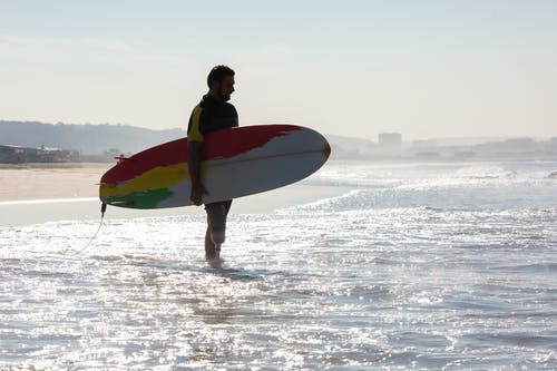 Silhouette of male amputee surfer with surfboard standing on beach
