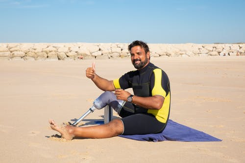 Side view full length handsome ethnic man with leg prosthesis resting on sandy seashore and showing thumb up gesture while looking at camera with smile