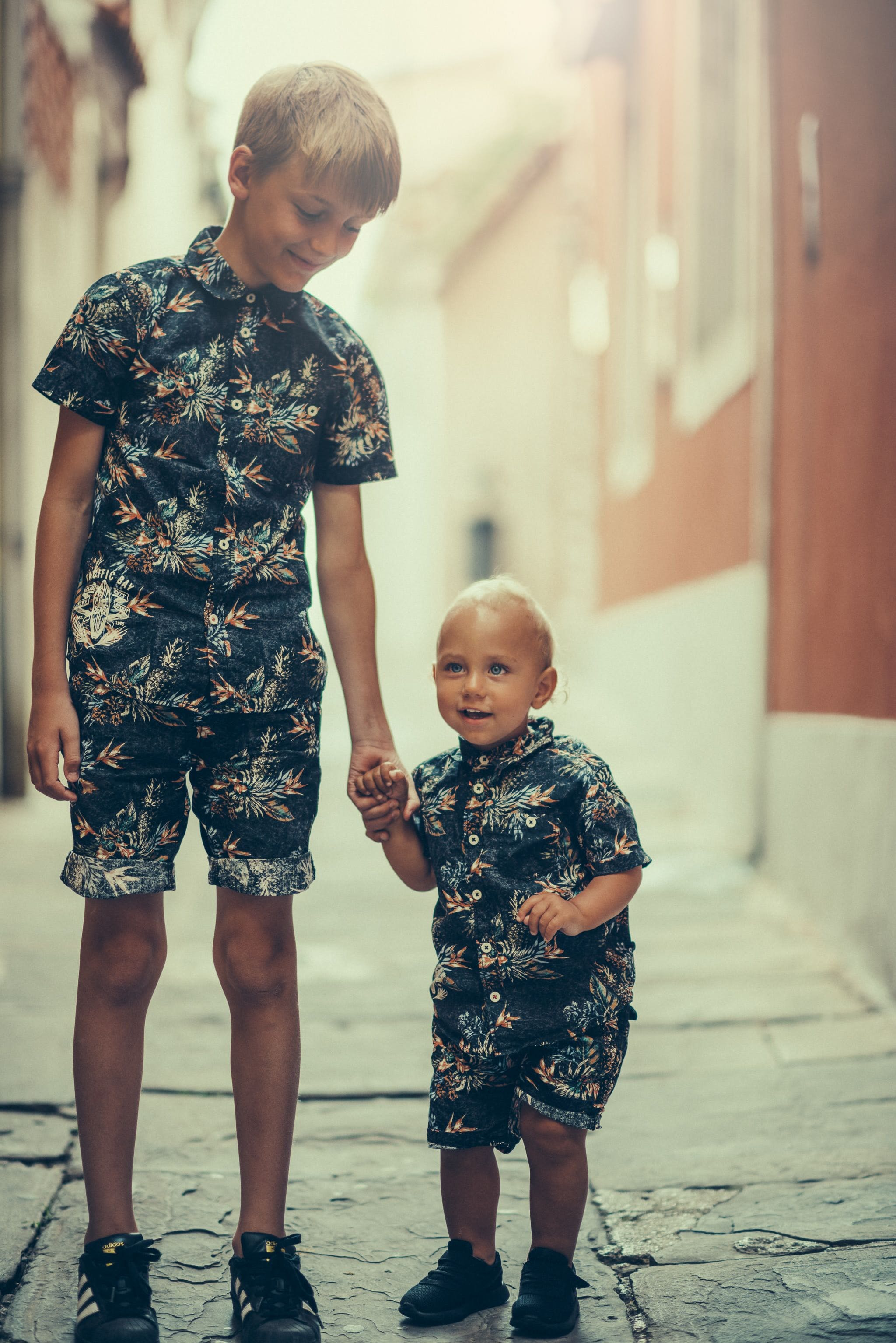 Selective Focus Photography of Boy Holding Child's Hand