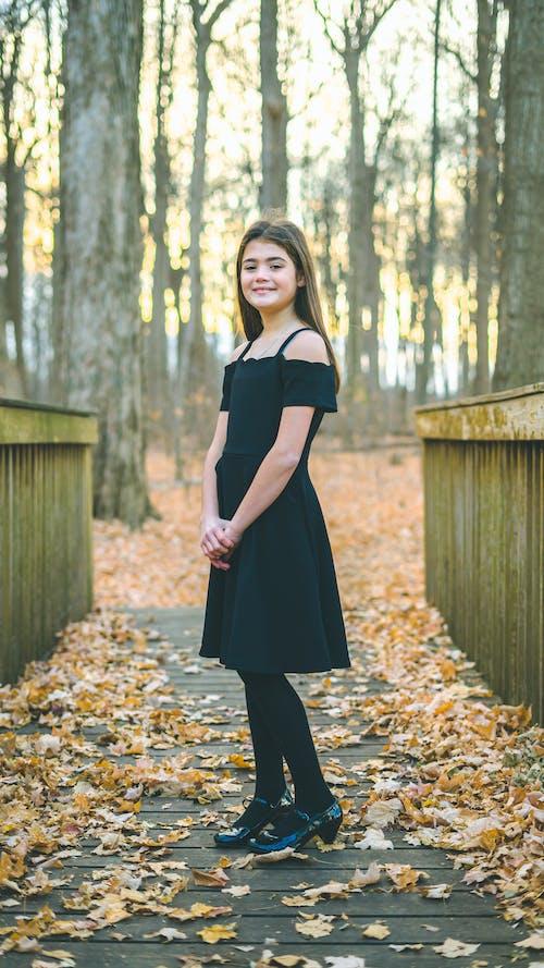 Calm girl in black dress standing in autumn park in sunlight