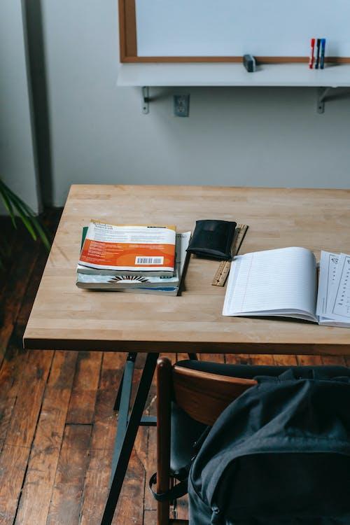 School desk with copybooks in modern classroom