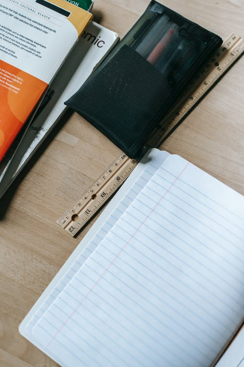 Opened copybook on desk with stationery
